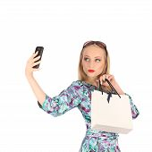 Beautiful Girl Holding Shopping Bags And Taking Selfie With Cell Phone Isolated