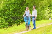 Two Young Romantic Lovers Spending Their Time In Summer Forest Outdoors With Bicycle