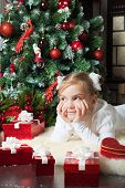 Pretty Girl With Gift Dreaming Near Christmas Tree