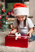 Little Girl In Santa Hat Opens Red Gift Box For Christmas