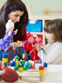 Female Teacher And Little Girl Playing In Kindergarten