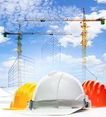 Safety Helmet Against Sketching Of Building Construction With Lifting Crane Use For Civil Engineerin