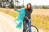 Happy brunette girl at cycling on dirt road