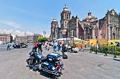 Police motorbike and people in Plaza de la Constitucion, in front of Cathedral Metropolitana in Mexi