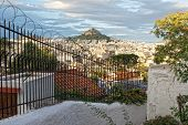 Fence With Barbed Wire On The Background Of Mount Lycabettus