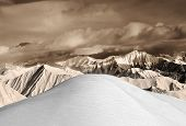 Top Of Off-piste Snowy Slope And Sepia Mountains