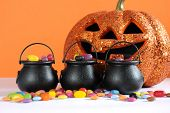 Happy Halloween Candy In Trick Or Treat Carry Cauldrons With Pumpkin On Orange Background.