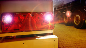 stock photo of truck-stop  - Glowing tail lights of parked truck on sunset - JPG