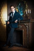 Young handsome man in elegant suit stands by the fireplace in a room with classic vintage style. Fashion.