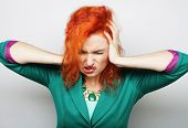 young redhair  woman with a headache holding head