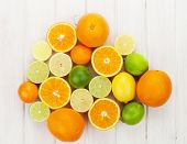 Citrus fruits. Oranges, limes and lemons. Over wooden table background