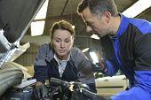 Mechanics instructor teaching woman in apprenticeship