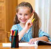 Schoolgirl with colored felt-tip pens in the classroom