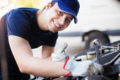 Smiling mechanic servicing a car engine