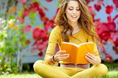 Young Nice Attentive Woman Lies On Green Grass And Reads Book Against Autumn  Park.