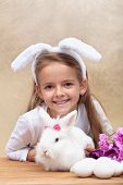 Happy little girl with bunny ears and her cute white rabbit preparing for easter