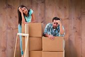 Stressed young couple with moving boxes against wooden planks