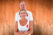 Mature couple supporting aids awareness together against wooden planks