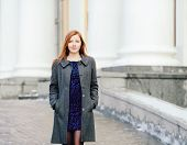 Portrait of young beautiful redhead lady in blue dress and grey coat on the porch at winter outdoor