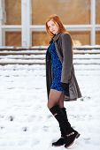 Full length portrait of young cute redhead woman in blue dress and grey coat at winter outdoors