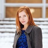Closeup portrait of young beautiful redhead lady in blue dress and grey coat at winter outdoors