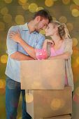 Attractive young couple leaning on boxes with piggy bank against close up of christmas lights