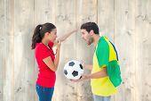 Brunette sending off a brazilian fan against pale wooden planks