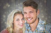 Attractive young couple smiling at camera against black abstract light spot design