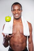 picture of throw up  - Young muscular African man with towel on shoulder throwing up an apple and smiling at camera while standing against grey background - JPG