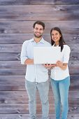 Attractive young couple holding their laptop against faded grey wooden planks