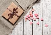 Gift box with heap of small hearts on white wood table.