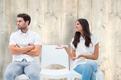Brunette pleading with angry boyfriend against pale wooden planks