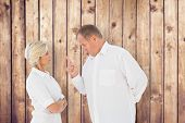 Angry man pointing at his partner against wooden planks