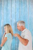 Angry man pointing at his wife against wooden planks