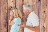 Angry man shouting at his wife against wooden planks background