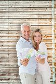 Happy couple flashing their cash against faded pine wooden planks