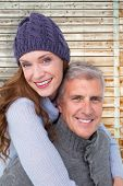 Happy couple in warm clothing against faded pine wooden planks