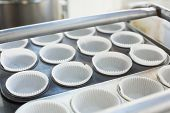 Cupcake holders in trays in the kitchen of the bakery