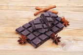 split bar of dark chocolate on wooden table