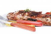 main course isolated on white: whole fryed sunfish on plate with lemons and peppers