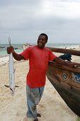Black Fisherman From The Island Of Zanzibar Holding Mackerel