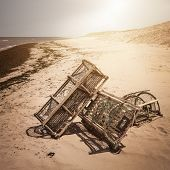 Three lobster traps on Atlantic ocean beach in Prince Edward Island, Canada, square format