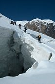 stock photo of crevasse  - Mountaineers crossing huge crevasse at 4600m on Lenin peak - JPG