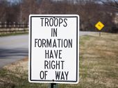 A close up of a metal sign that says Troops In Formation Have Right Of Way along the side of a road.