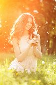image of dandelion  - Young spring fashion woman blowing dandelion in spring garden - JPG