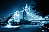 Tower Bridge and statue of a girl playing with dolphin in St Katharine docks in London.