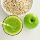 high-angle shot of an apple, a glass with a green smoothie and a bowl with oatmeal cereal on a white table