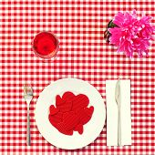 high-angle shot of a plate full of red hearts with different size on a set table with a checkered red and white tablecloth