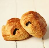 Two pain au chocolat, french pastry on white wooden background