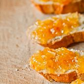 pieces of baguette with orange marmalade closeup on wooden board
